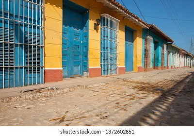 Empty street scene in Trinidad Cuba lined with bright homes and security grills.