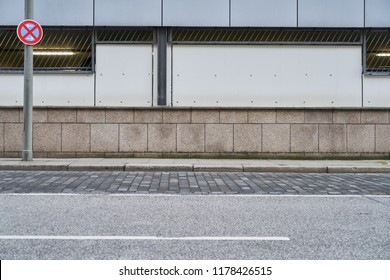 Empty street and sidewalk in front of a wall in the city of Hamburg - Shutterstock ID 1178426515