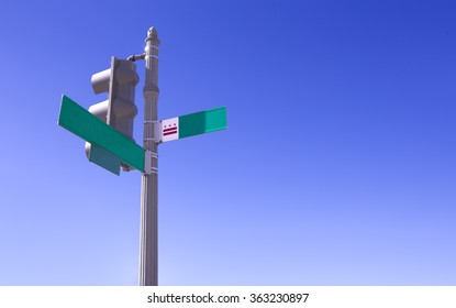 Empty street sign and traffic light over deep blue sky.