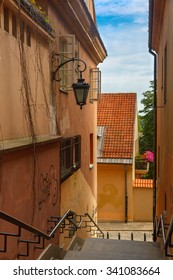 Empty street with stairs and lantern in the Old Town of Warsaw in the summer sunny day, Poland