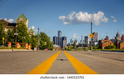 An empty street through an old Detroit city neighborhood with downtown buildings in the background