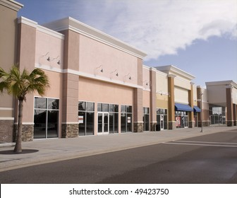 empty strip mall with pastel stucco and stone accents