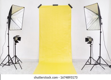 Empty studio with yellow backdrop and light equipment. Copy​ space​ for​ text or​ mock-up