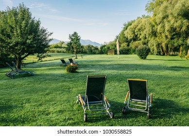 Empty sunbeds on green grass in summer morning garden with beautiful view