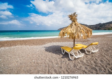 Empty sunbeds and umbrella on Vlycha beach near Lindos village (Rhodes, Greece)