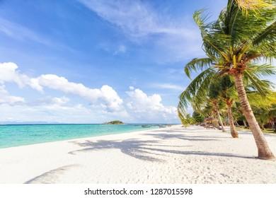Empty sunny Koh Lipe Beach with tall palms and beach bungalows