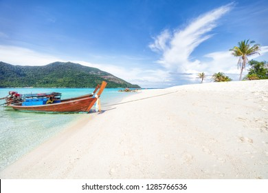 Empty sunny Koh Lipe Bulow Beach panorama with long tail wooden boats
