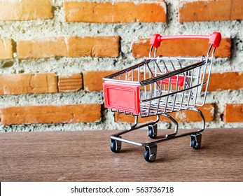 Empty supermarket shopping trolley mini cart on wooden ground with blur old brick block and light flare.