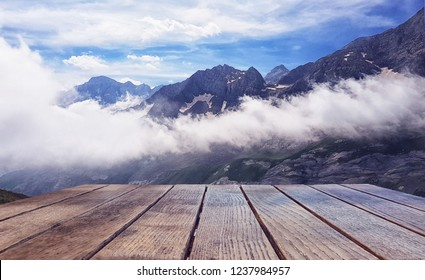 Empty surface of the wooden table against the background of a landscape of snow-capped mountains