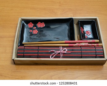 empty sushi set in cardbox as gift - dishes, bamboo chopsticks and black red mat. low angle close shot