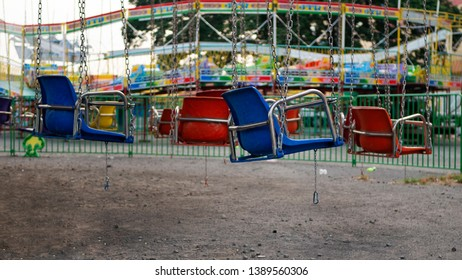 Empty suspended carousel chairs in a deserted amusement park.