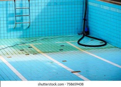 Empty swimming pool with broken tiles with metal ladder waiting for repair.