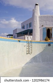 Empty swimming pool with traditional Greek Cycladic island house in the background.