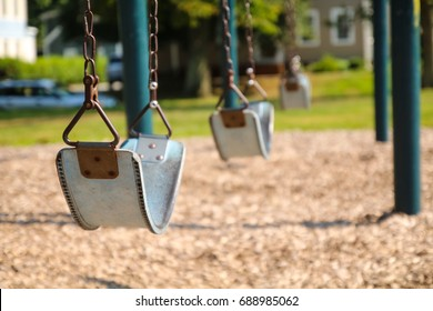 An empty swing set at a playground. The swings have no children playing on them. Back to School concept.