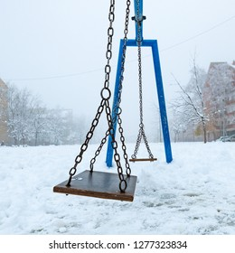 Empty swing in winter with snow covering children's playground