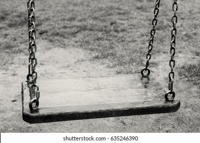 Empty swings. The Lost Child. Black and white image.