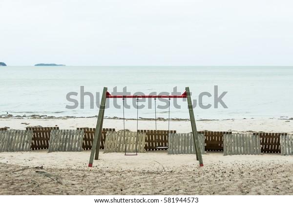 Empty swings on empty sandy beach