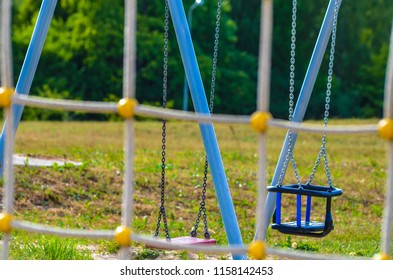 Empty swings in playground. No kids at all.