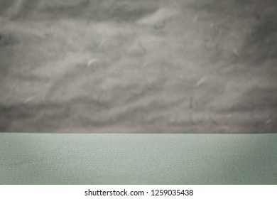Empty table background with tablecloth and uneven wall