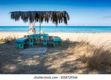Empty table and bench on beach, Crete, Greece