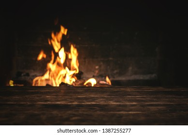 Empty table with a copy space for food for example over a burning fire in a brick fireplace.