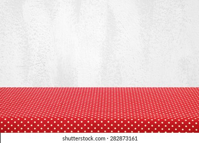 Empty table covered with red polka dot tablecloth over white cement wall background, for product display montage