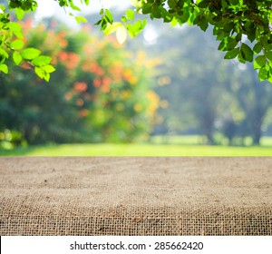 Empty table covered with sackcloth over blurred trees with bokeh background, product display template