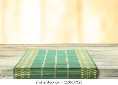 Empty table with green tablecloth over bright background. For your food and product display montage