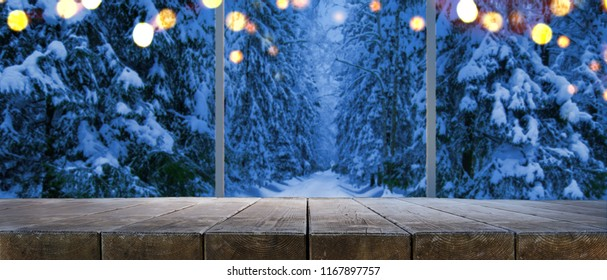 Empty table at home with panoramic view through window of snowy trees in winter forest background