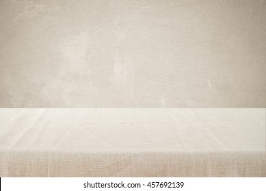 Empty table with linen tablecloth over brown cement wall background, product display montage