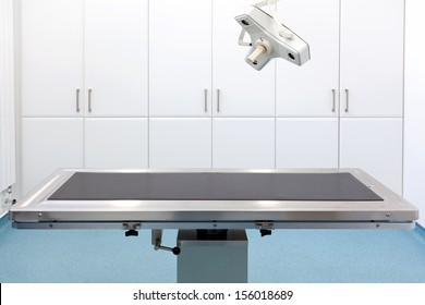 Empty table in an operating room with light above.