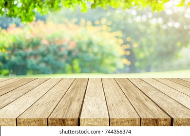 Empty table, perspective wood over blur tree with bokeh background, product display montage background