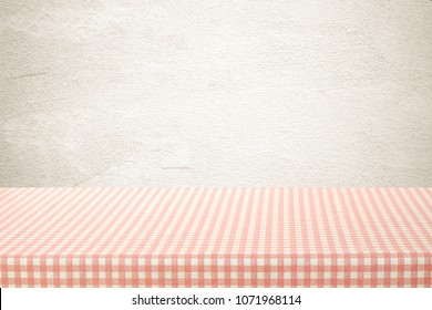 Empty table with pink and white check pattern tablecloth over brown wall background, banner, table top, shelf, counter design for product display montage