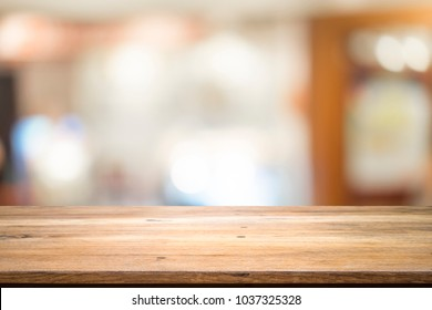 Empty table for present product with blured background of coffee cafe.