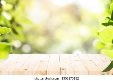 Empty table for present product with green bokeh out of focus background from nature forest.