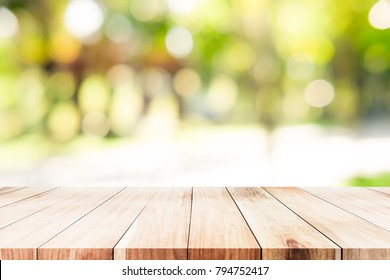 Empty table for present product with green bokeh out of focus background from nature forest