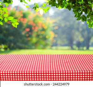 Empty table and red tablecloth with blur green leaves bokeh background, for product display montage