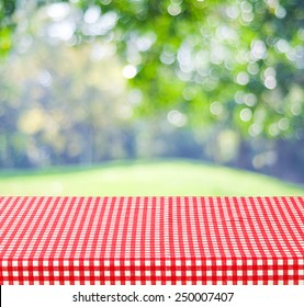 Empty table and red tablecloth over blur tree and bokeh background, for product display montage