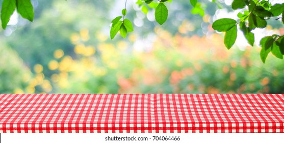 Empty table with red tablecloth over blur green tree and bokeh background, for food and product display montage background, banner