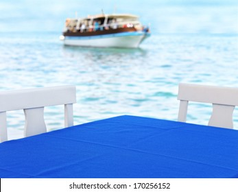 empty table from a restaurant nearby the sea port in Greece