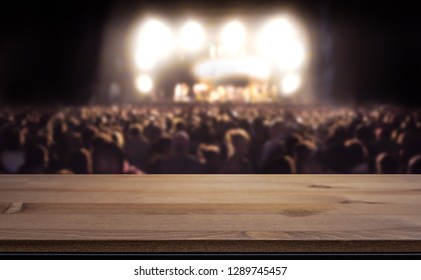 Empty table top for product display montage. Crowd at concert, summer music festival blurred in the background.