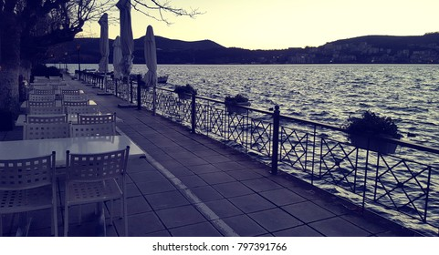 Empty tables and chairs in a row along the lake shore in Kastoria town, Greece