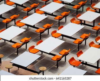 empty tables chairs set in rows of large university school canteen lunch room easy clean industrial style design white top plate orange plastic seats on fixed metal frame construction top view