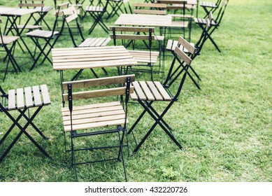 Empty tables and chairs standing on grass in summer cafeteria