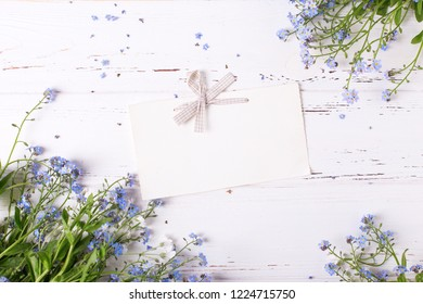 Empty tag and frame  from  blue forget-me-nots or myosotis flowers on  white wooden background. Floral still life. Selective focus.  View from above.