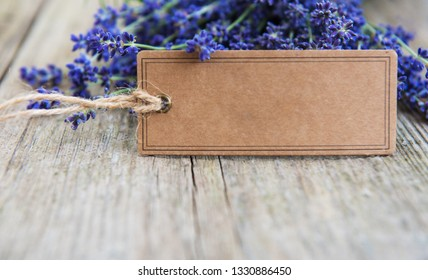 Empty tag and lavender flowers on a old wooden table
