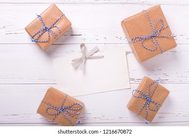 Empty tag and wapped gift boxes with presents on textured wooden background. Selective focus is on tag. Place for text. Flat lay.