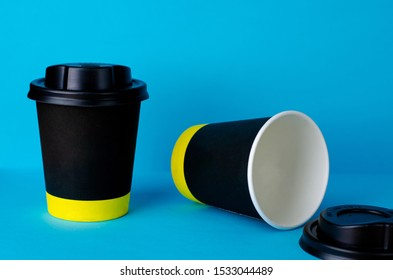 Empty take away coffee paper cup on blue background. Copy space mock up