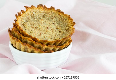 Empty tartlet in a white bowl, creased table cloth in the background