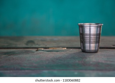Empty tea cup from stainless steel kept on old wooden table, India